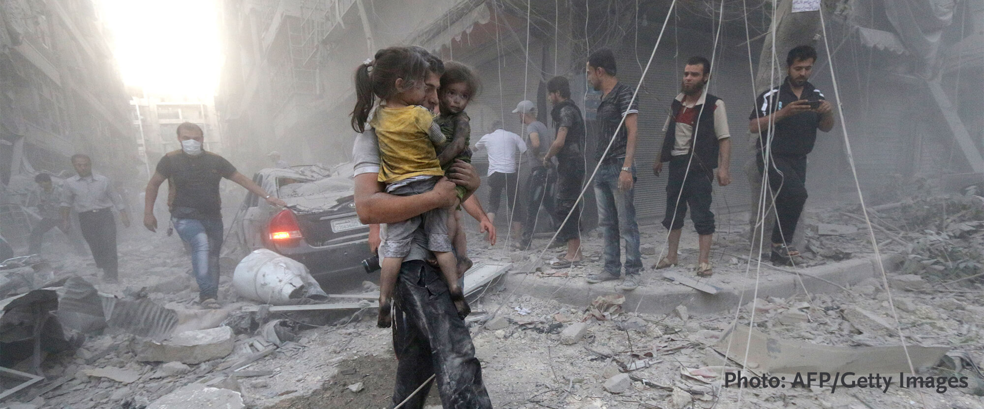 Syrian man carrying child through building rubble in Syria